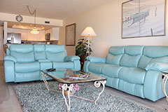 A teal couch set in Surfside 302 a 2 bedroom 2 bath beachfront vacation condo with a private balcony